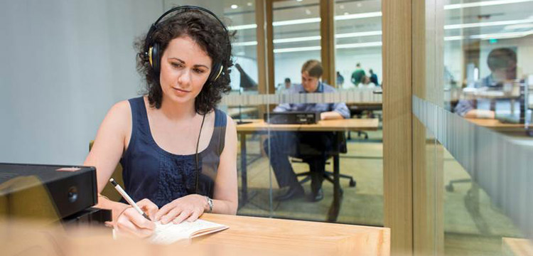 Female researcher studies at desk in National Library reading room
