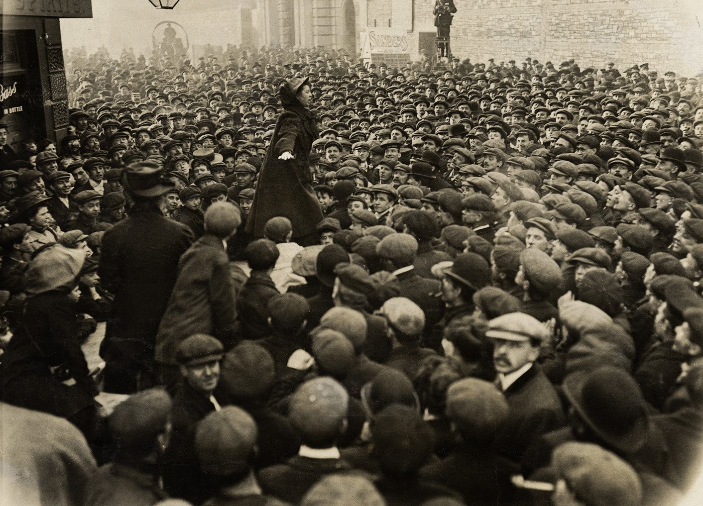 A woman standing with her arms stretched out speaking to a crowd of men outside a factory