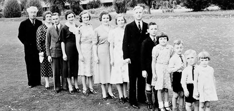 family photograph. family members lined up in descending order largest to smallest. outside on a grassed area in front of trees.