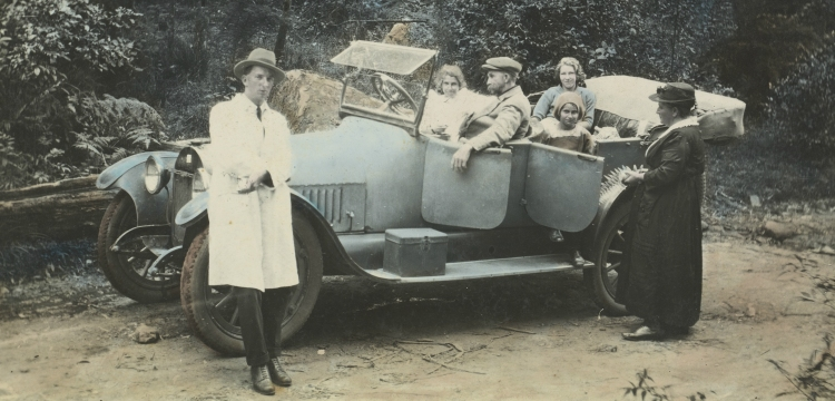 Family group seated and standing beside an open touring car, New South Wales  between 1910 and 1925, nla.obj-153091595