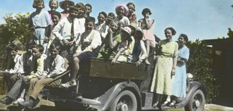 Group of children and two women standing on tray of car