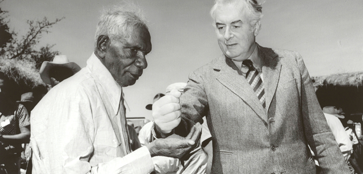 Prime minister Gough Whitlam pours soil into the hand of Gurindji Traditional Land Owner Vincent Lingiari at Wattie Creek, Northern Territory, 16 August 1975