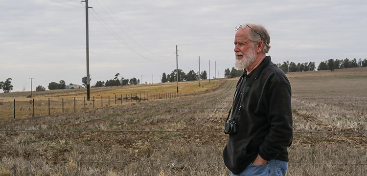 A man standing with his hands in his pockets in a dry paddock