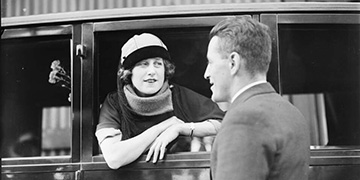 Actress Dorothy Brunton leaning over a windowsill to chat to a gentleman, ca. 1925'