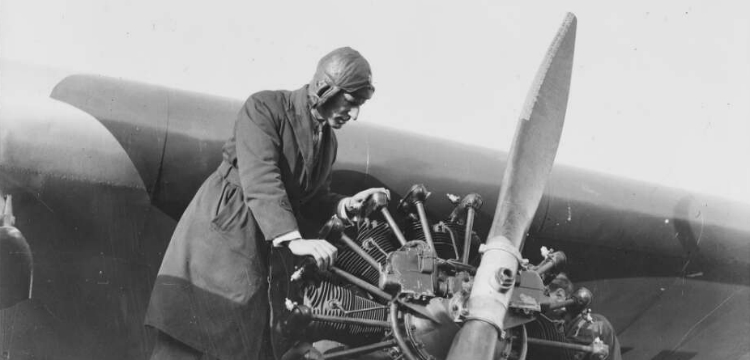 Charles Kingsford Smith examining the propeller of a plane