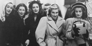 six women wearing coats