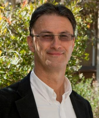 Professor Matthew Ricketson. Photograph of the head and upper body of Professor Matthew Ricketson, green foliage in the background