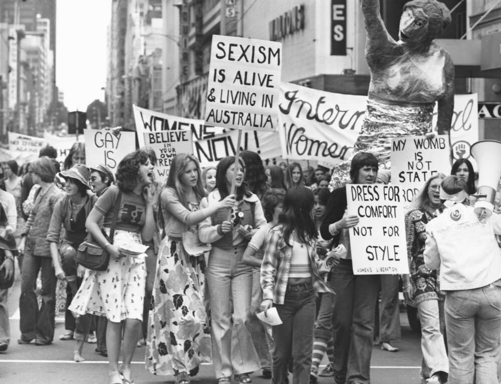 Women on the march wave their placards at the International Women's Day march, Melbourne, March 8, 1975 [picture] / Australian Information Service photograph by John McKinnon