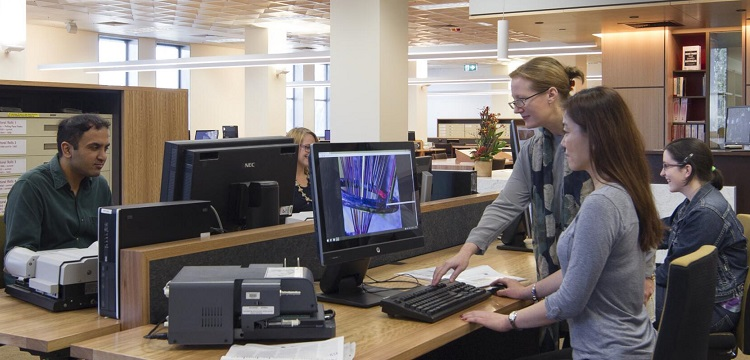 People using computers and microfilm readers