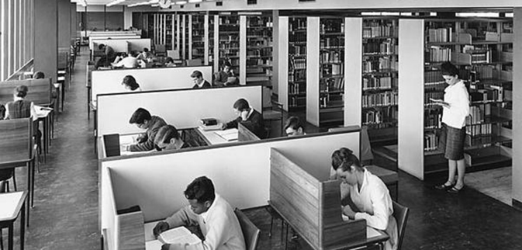 Students in desks and browsing library shelves in Monash University Library