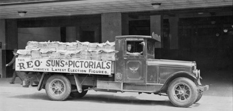 man in a truck stacked full of newspapers