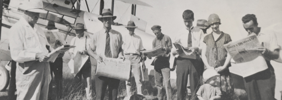A group of men holding newspapers in front of airplane