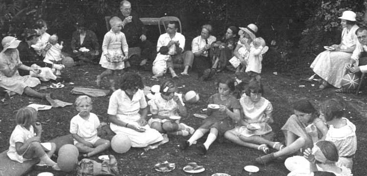 Image of a group of people seated on lawn eating food