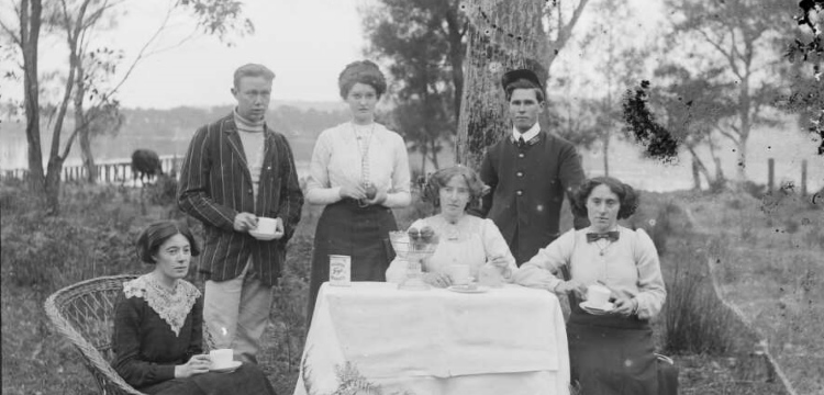 Group around outdoor table, possibly having afternoon tea