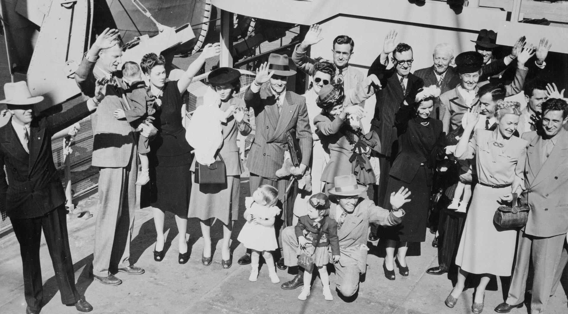 Families standing on a dock, smiling and waving.