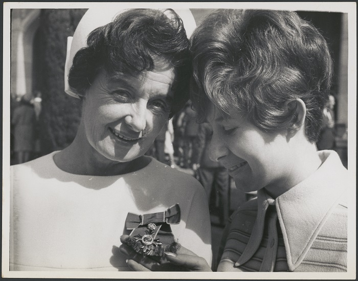 black and white photograph of two women, Hazel de Berg and her daughter Diana, showing Diana admiring Hazel's new medal for her MBE