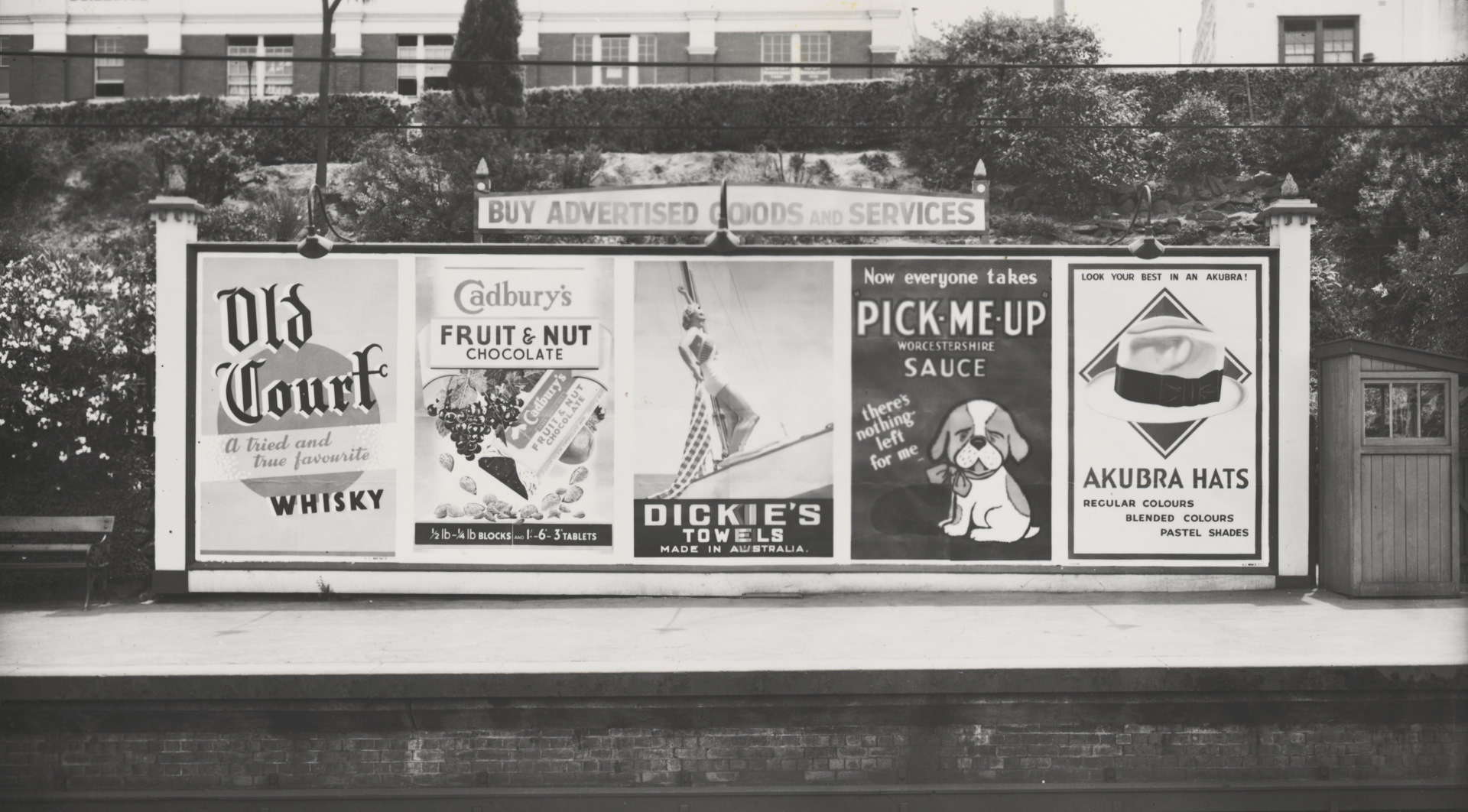 Advertising billboard for Old Court whisky, Cadbury's chocolate, Dickie's towels, Pick-me-up Worcestershire sauce and Akubra hats on railway platform, Melbourne, ca. 1930
