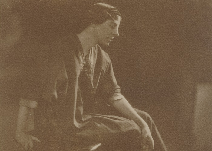 Sepia photograph of Marion Mahony Griffin, seated and in profile, with her back arm resting on her knees and front arm on the stool she is sitting on. She wears a long, loose dress.