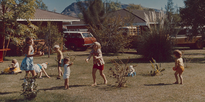 7 children playing in the front yard of a suburban house, throwing a colourful ball and driving toy cars