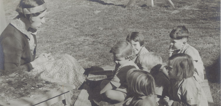 [Photograph of children seated on a blanket next to a woman,] listening to a story [picture]. nla.obj-231610278