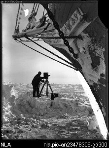 Frank Hurley with camera on ice in front of the bow of the trapped  Endurance