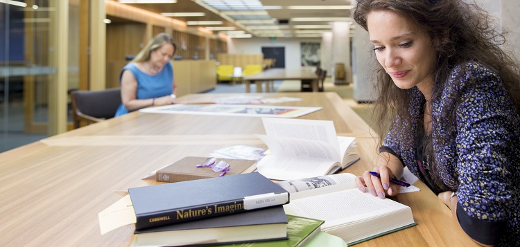 Two people using collection material in the Special Collections Reading Room at the National Library of Australia