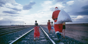 Santa and children walking along tracks