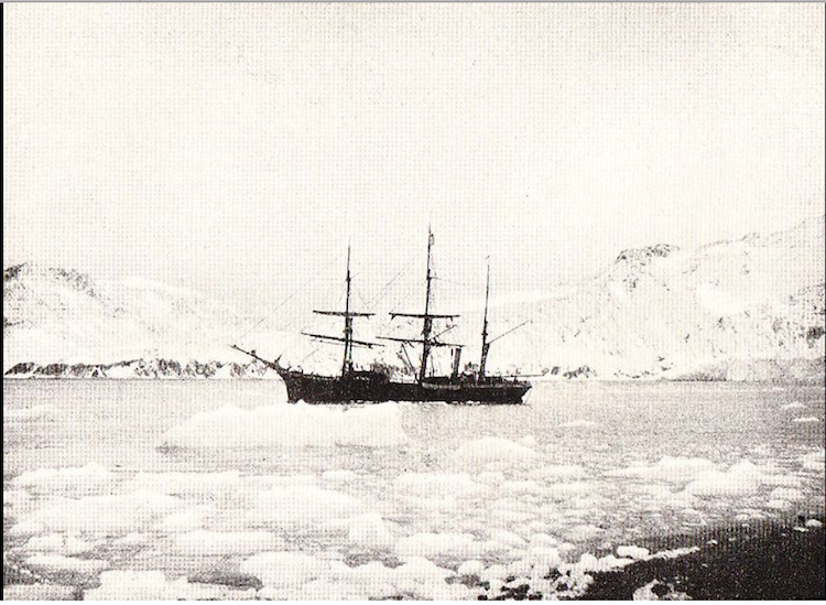 A black and white picture of a ship sailing through ice with Antarctica in the background