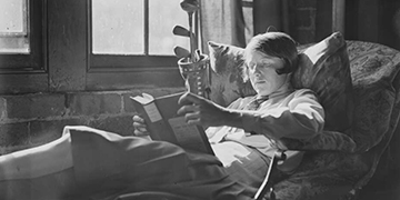 Vintage photo of a woman reclining and reading a book