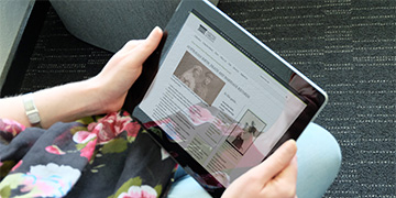 Woman viewing the NLA Research Guides webpage on an iPad.
