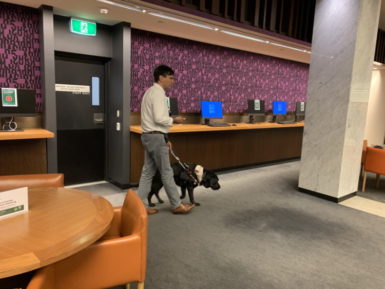 Scott Grimley walking with dog in Library