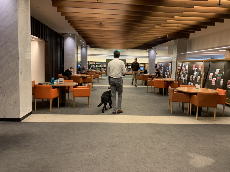 Scott Grimley walking with his guide dog through Main Reading Room