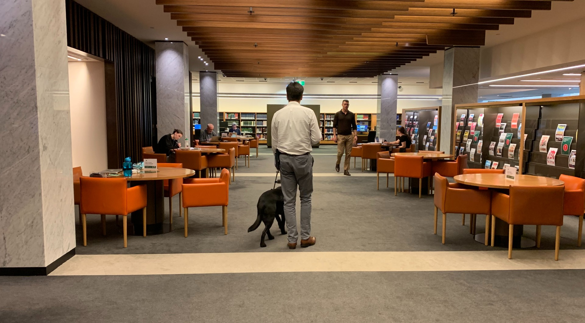 Photograph of Scott Grimley with Dudley, a black dog, walking through the Library's main reading room