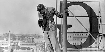 a man near the top of a building pointing a camera to the ground