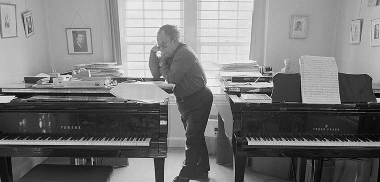 Professor Larry Sitsky. Photograph of Professor Larry Sitsky leaning on a piano, reading. Another piano is behind him with sheet music on the stand. Stacks of paper and books are near him.