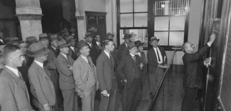 Crowd of men watching a man write on a blackboard at the Sydney Stock Exchange