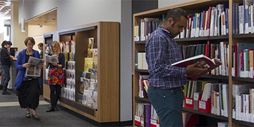 Man looking at books on shelf