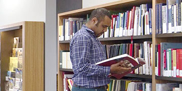 A person browsing the shelves at the Library