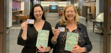 Kate Forsyth and Belinda Murrell holding Library cards in front of the Main Reading Room