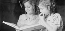 Portrait of two girls, Adelie and Toni Hurley, reading a book