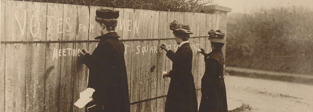 Three suffragette's writing chalk graffiti on a wall