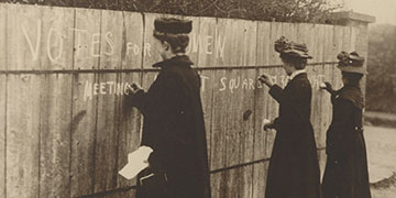 Three Women Writing Pro-suffragette Graffiti on a Wall in Chalk