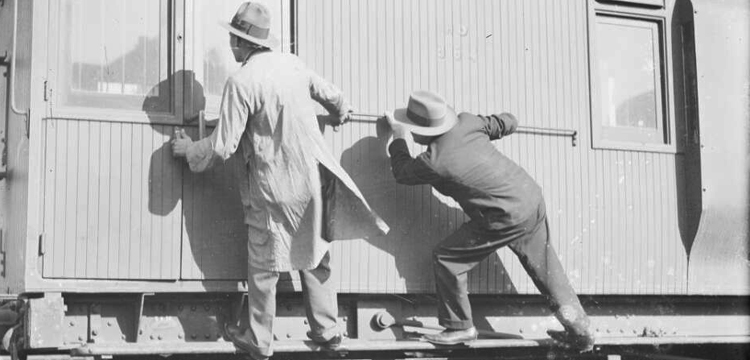 Two men trying to open the door of a goods train