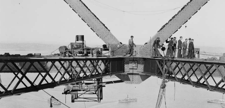 Group of men standing on a metal dirgle during the construction of the Sydney Harbour Bridge