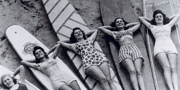 5 women in swimsuits lying on surboards