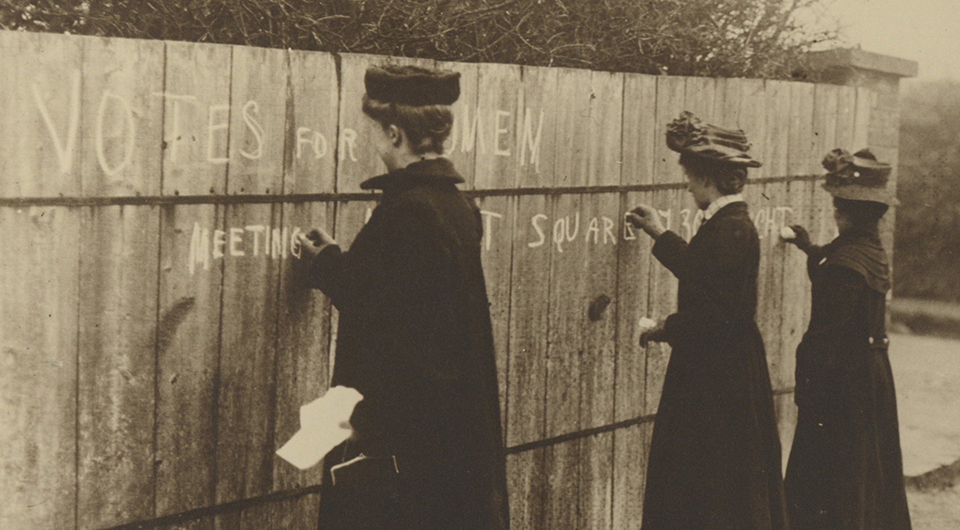 Suffragists writing on fences