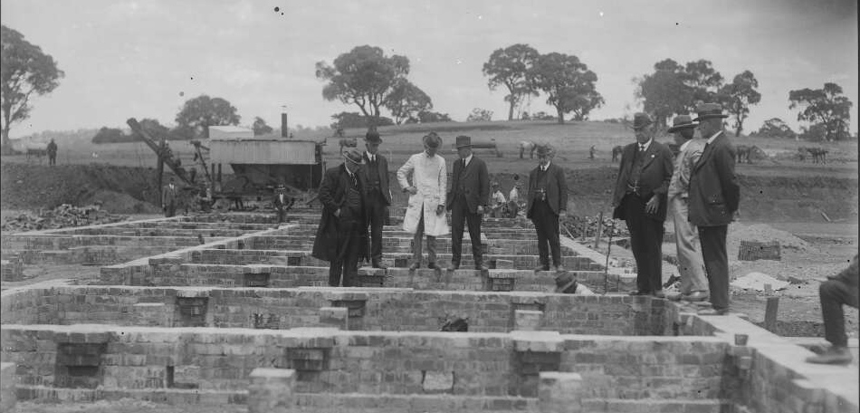 Members of the federal cabinet standing on the newly laid foundations of Parliament House, Canberra, ca. 1924