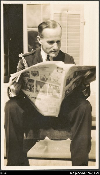 Unidentified aviator in uniform sitting on steps reading a newspaper, ca. 1930 [picture].
