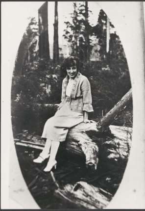 Woman sitting on a fallen mountain ash log