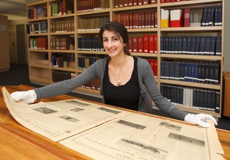 Vicky Dimcevska looking at historic newspaper in National Library Newspaper Reading Room